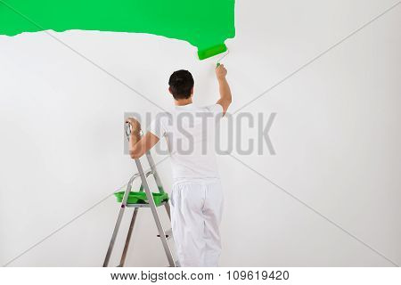 Man Painting Wall With Green Paint Roller