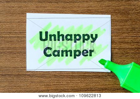 unhappy camper word highlighted on the white paper poster