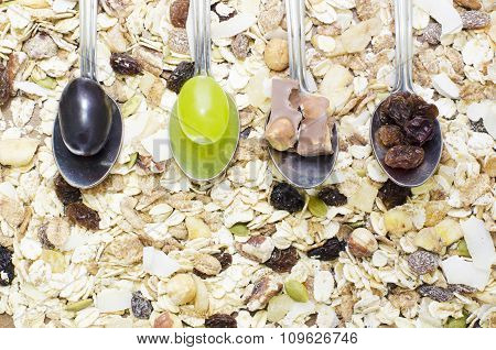 Spoons on a cereal background with grapes, chocolate,