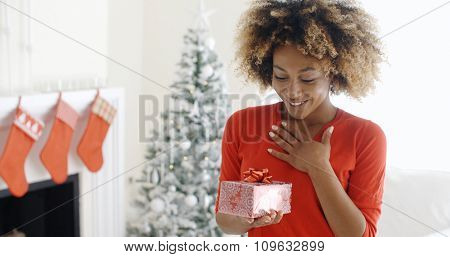 Excited young woman with an unexpected Christmas gift holding her hand to her chest with a look of surprise  decorated Christmas tree and fireplace behind