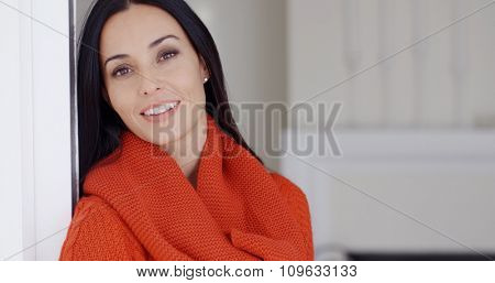 Gorgeous young woman standing leaning against a wall daydreaming looking up into the air with a gentle smile of pleasure and a faraway look  with copyspace.