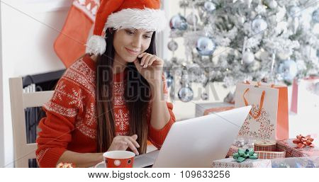 Smiling young woman surfing the internet on her laptop computer for Christmas bargains as she sits at a table in front of the decorated tree in her red Santa hat.