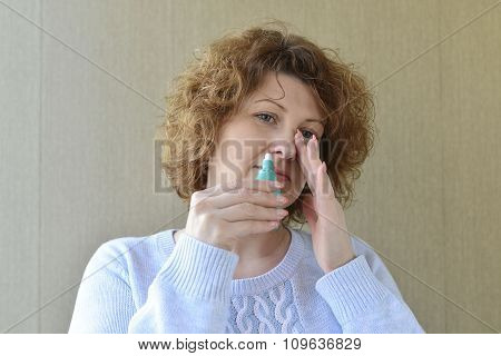 Sick with  rhinitis woman dripping nose medicine