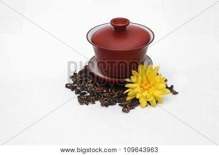 Ceramic gaiwan full of green tea  with a  cover and a pile tea leaves with yellow flower