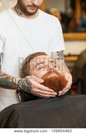 Cheerful male barber is serving his customer