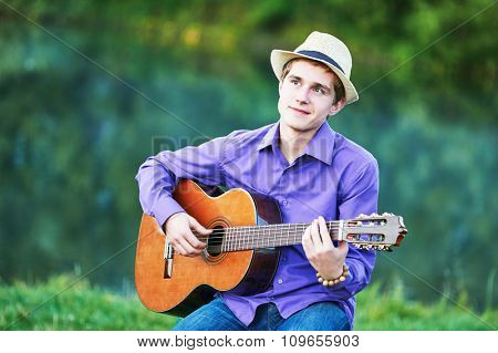 young man playing acoustic six string guitar on a bench outdoors