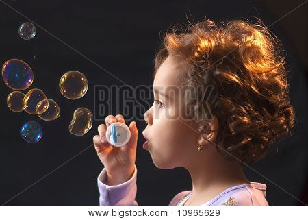 Little Girl Playing With Soap Bubbles