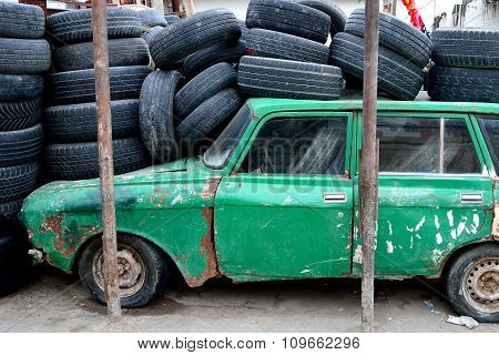 Old green Azerbaijani car in Baku, under a pile of tyres, from the side