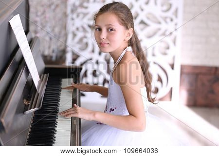 Attractive little princess girl plays piano