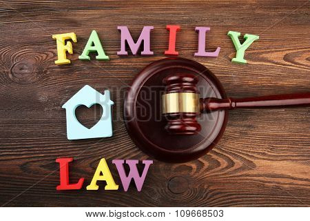 A gavel, a silhouette of a house and colourful letters regarding child-custody and family-law concept