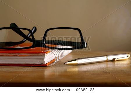 Eyeglasses, notebook and a pen