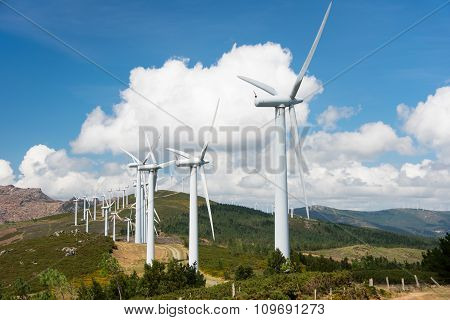 Large turbines of windmill powered plant on hilltop in Europe poster
