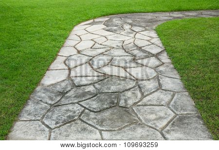 The Stone block walk path in the park with green grass background