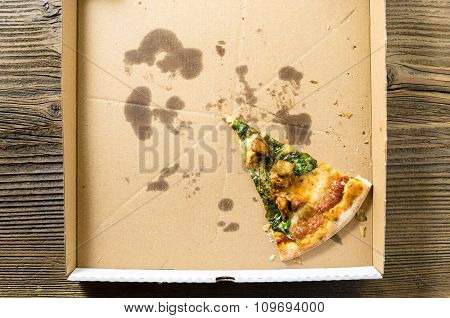 One piece of pizza in cardboard pizza box. Top view