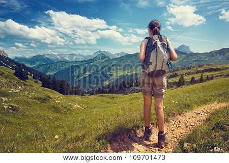 Full Length Rear View of Female Hiker Wearing Backpack Pausing on Trail to Admire View of Lush Green Mountain Valley on Bright Sunny Day