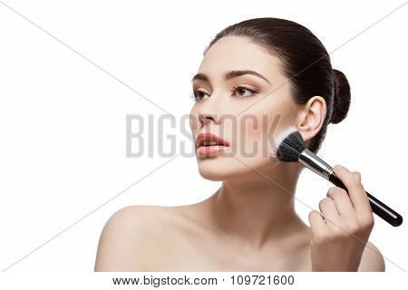 Beautiful girl applying powder with brush