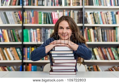 Smiling Young Girl Sitting At A Desk In The Library With Her Arms On A Big Pile Of Books And Chin On