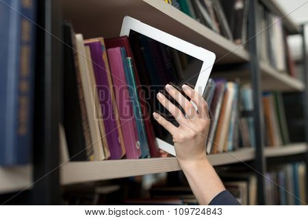 A Tablet Picked With A Hand From A Book Shelf In The Library, A Concept Of Learning And Choice