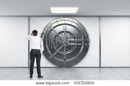 Man Sratching Head With Left Hand Standing In Front Of A Big Locked Round Metal Safe In Bank Deposit