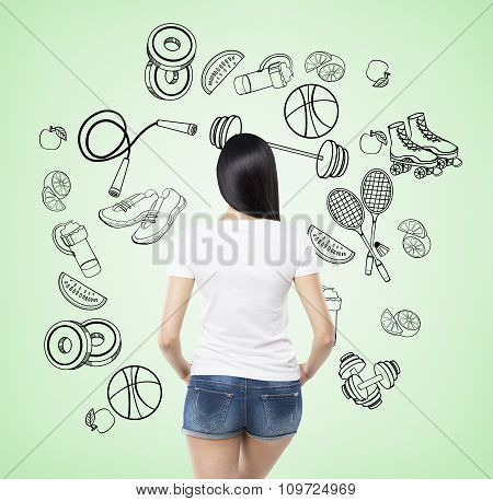 A Rear View Of A Brunette Lady Who Is Trying To Make A Choice In Favour Of A Certain Sport Activity.