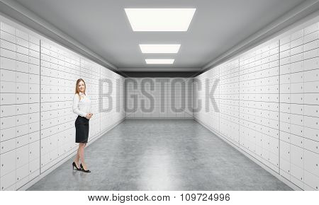 A beautiful private manger of a bank is standing in a room with safe deposit boxes. A concept of storing of important documents or valuables in a safe and secure environment. poster