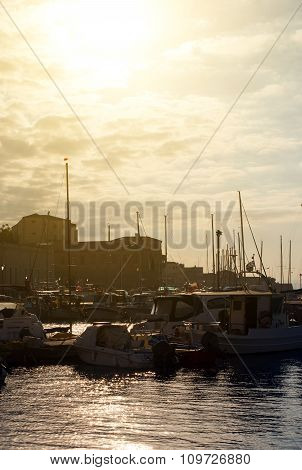 Many yachts and boats in the harbor at sunset.