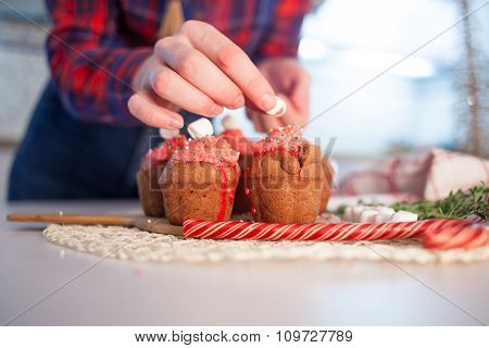 Girl decorates New Year celebration cupcakes, chocolate muffins on table