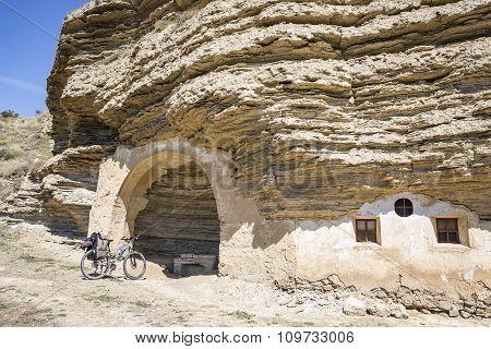hermitage Virgen de la Peña carved in the rock and a bike - Tosantos, Burgos, Spain