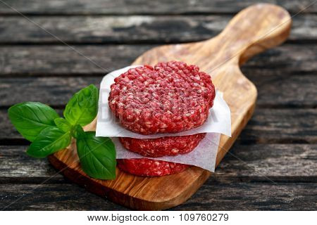 Home HandMade Minced Beef burgers on cutting board. old wooden table