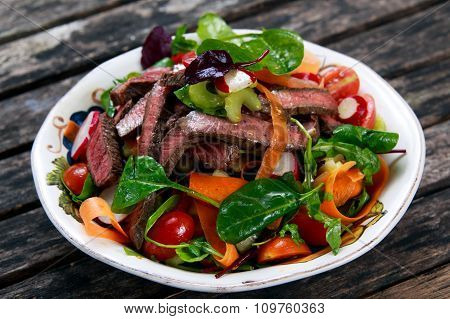 Spicy Beef Slices Meat Salad with Carrots, Tomatoes, Cucumber, Parsley and Salad leaves Spinach, roc