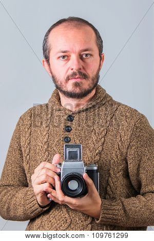 Man with beard in sweater holding old analogue medium format camera