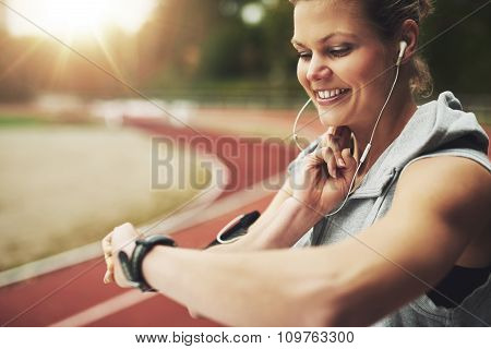 Smiling Athletic Woman Looking At Her Watch And Feeling The Pulse On Track Field