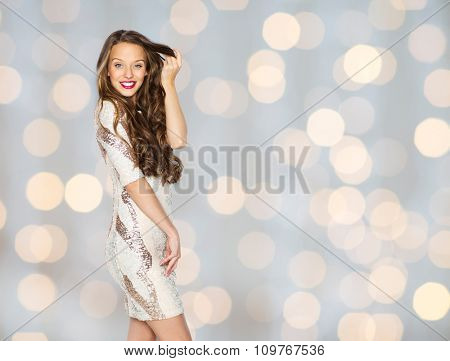 people, style, holidays, hairstyle and fashion concept - happy young woman or teen girl in fancy dress with sequins touching long wavy hair over lights background
