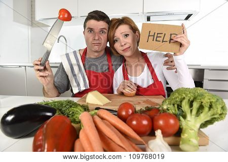 young attractive American couple in stress at home kitchen looking lost and frustrated wearing apron asking for help unable to cook in amateur newbie inexperienced and rookie home cooking mess poster