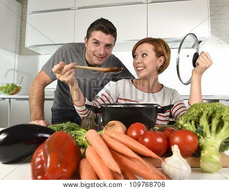 Young Attractive Couple At Home Kitchen With Man Tasting Vegetable Stew Cooked By Her Wife Smiling H