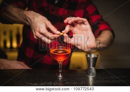 Bartender Is Squeezing Orange Peel Into A Cocktail Glass