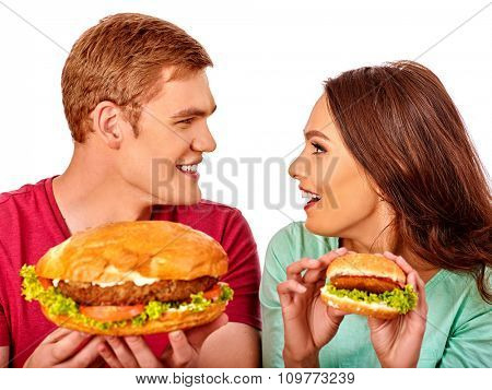 Young couple man and woman eating hamburgers big and small   . Fastfood concept.  Isolated.