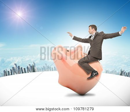 Man sitting on pink piggy bank