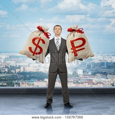 Man holding moneybags with dollar and ruble signs