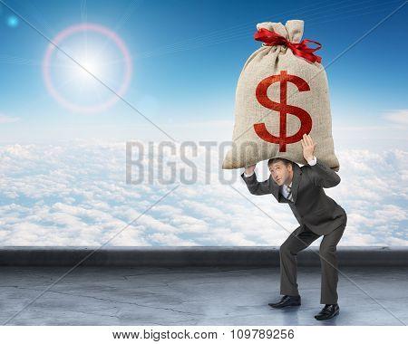 Businessman holding heavy moneybag