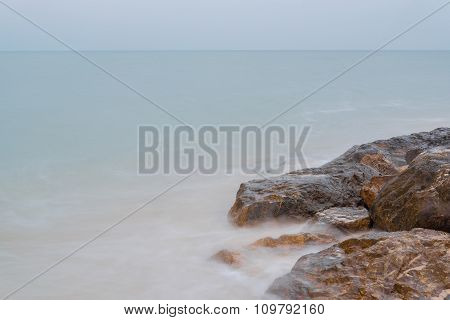 Motion blur of stones on the sea beach under Cloudy sky with long exposure effect.