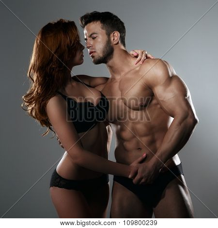 Passionate couple in studio on a gray background poster
