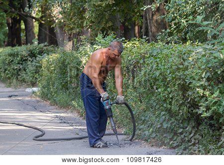 Kiev, Ukraine - September 01, 2015: Worker Using A Jackhammer To Remove The Asphalt Road Repair