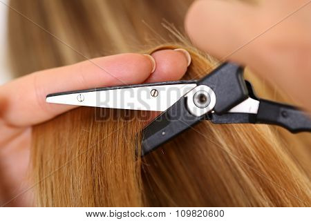Female Hand Holding Hot Thermal Scissors Cutting Lock Of Long Straight Blonde Hair