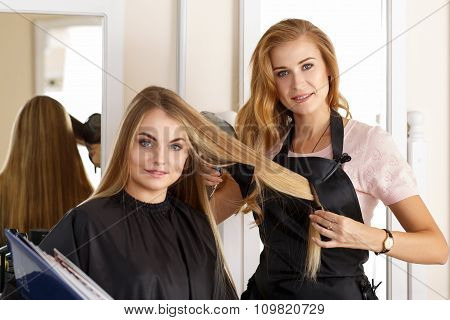 Beautiful Blonde Female Hairdresser Holding Scissors, Comb And Hairdryer In Hands