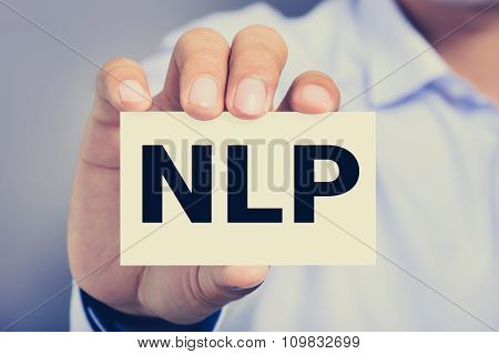 Nlp Letters (or Neuro Linguistic Programming)  On The Card Shown By A Man