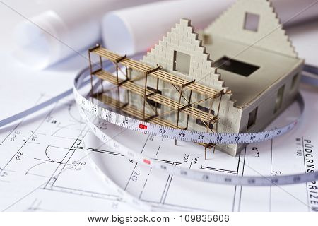 New Model House With Scaffolding On Architecture Blueprint Plan At Desk - Construction Site