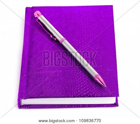 purple notebook with silver pen