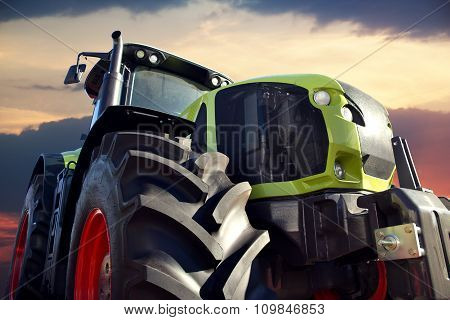 Farm Tractor Working At Sunset