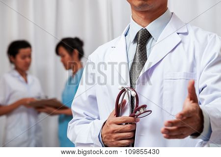 doctor holding stethoscope and handing one hand